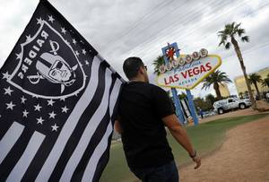 Matt Gutierrez carries a Raiders flag by the sign welcoming visitors to Las Vegas, Monday, March 27, 2017. NFL team owners approved the move of the Raiders to Las Vegas in a vote at an NFL football annual meeting in Phoenix.