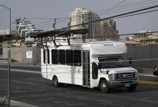 A downed power line rests on a bus along a road, Thursday, March 30, 2017, in Las Vegas. High winds are being blamed for multiple scattered power outages affecting almost 40,000 NV Energy customers in the Las Vegas area.