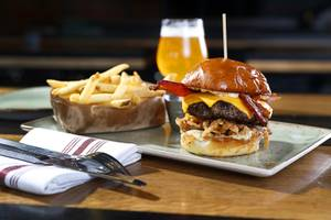 The White Truffle Bacon Aioli Burger at Public School 702 in Downtown Summerlin Monday, April 17, 2017. The bacon and cheese burger with a white truffle and cherry vinaigrette aioli is served on crispy onion straws. Paired with your choice of three beers, the burger and fries combo is $13.00 through April.