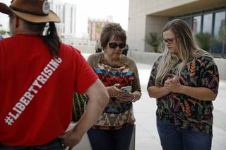 Carol Bundy, center, wife of Nevada rancher Cliven Bundy, looks at her phone beside Bailey Logue, daughter of Cliven Bundy, while waiting for a verdict outside of the federal courthouse, Monday, April 24, 2017, in Las Vegas. A jury found two men guilty of federal charges Monday in an armed standoff that stopped federal agents from rounding up cattle near Cliven Bundy's Nevada ranch in 2014. Jurors said they were deadlocked on charges against four other men, and the judge told them to keep deliberating.