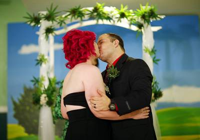 Natalie Rice, left, kisses her new husband, Lee Rice, beneath a canopy of faux marijuana plants during a ceremony at the Cannabis Chapel, Wednesday, April 20, 2016, in Las Vegas. Natalie and Lee Rice were the first couple to marry at the marijuana themed wedding chapel, which opened Wednesday.
