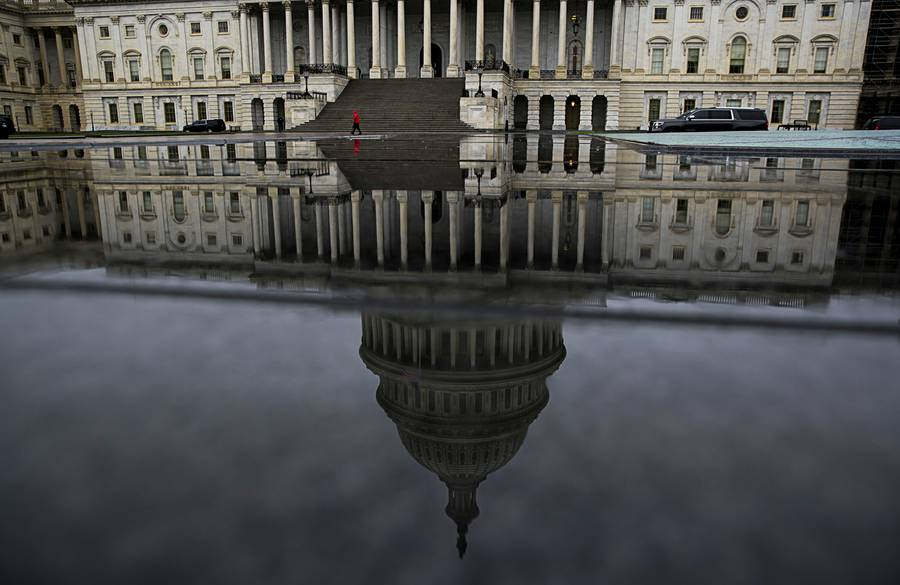 Seen in reflection, the Capitol building in Washington, April 24, 2017. The detail-light introduction of President Donald Trump's tax plan has left lawmakers and analysts with more questions than answers, but it has put into focus the many obstacles his plan would face.