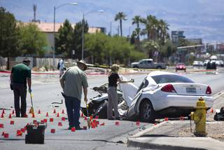 Metro Police investigators take measurements and photos following a fatal accident involving a car and a Clark County School District bus on Nellis Boulevard at Carey Avenue Thursday, May 4, 2017.