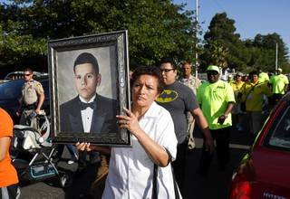 A family friend holds a portrait of slain teen Jose de Jesus Alatorre Guzman during a march and vigil in a neighborhood near Decatur Boulevard and Bonanza Road Monday, May 15, 2017. Alatorre Guzman, 19, was shot and killed in a drive-by shooting on May 11, 2016. The case is yet unsolved.