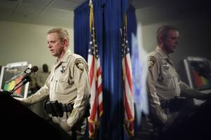 Las Vegas police Undersheriff Kevin McMahill is reflected in a television screen as he speaks during a news conference Wednesday, May 17, 2017, in Las Vegas. Police held the news conference to report on the investigation of the weekend death of an unarmed black man at a Las Vegas Strip casino at the hands of an officer using a neck hold that is banned in many cities. (AP Photo/John Locher)