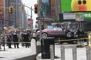 A car rests on a security barrier in New York's Times Square after driving through a crowd of pedestrians, injuring at least a dozen people, Thursday, May 18, 2017.  (AP Photo/Mary Altaffer)