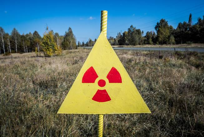 Radiation sign next to Red Forest in the Chernobyl Nuclear Power Plant Zone of Alienation, Ukraine.