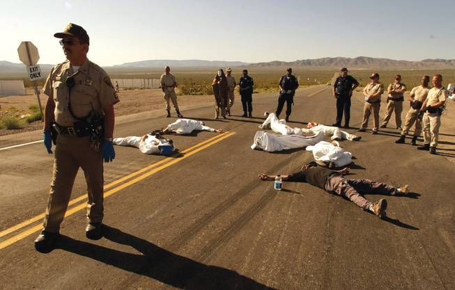 Protesters of the proposed Yucca Mountain nuclear waste repository and weapons testing lie on the pavement after crossing the line into the Nevada Test Site in Mercury. During the spring 2003 demonstration, 34 people were arrested for trespassing.