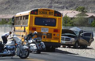 A mechanic, left, looks over a bus after an accident involving a Clark County School District bus and a SUV on Fort Apache Road near Post Road Thursday, May 25, 2017.