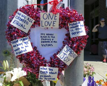 A heart-shaped wreath covered with positive messages hangs on a traffic light pole at a memorial for two bystanders who were stabbed to death Friday, while trying to stop a man who was yelling anti-Muslim slurs and acting aggressively toward two young women, including one wearing a Muslim head covering, on a light-trail train in Portland, Ore, Saturday, May 27, 2017.