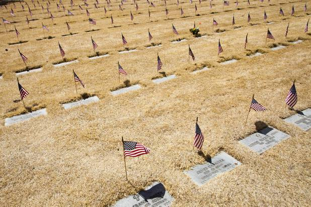 Flags stand over headstones during the Memorial Day Ceremony at the Southern Nevada Veterans Memorial Cemetery in Boulder City, NV, Monday, May 29, 2017. Large sections of grass at the Veterans Memorial Cemetery is being killed off for upcoming renovation efforts to raise the sinking headstone to ground level .