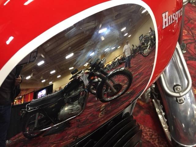 A 1973 Triumph Bonneville is reflected in the chromed fuel tank of a 1969 Husqvarna dirt bike at the Mecum Las Vegas Motorcycle Auction. Bidding in the event, being held at the South Point Exhibit Hall, is scheduled to begin Friday, June 2, 2017.