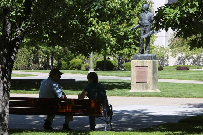 A man and a woman converse in front of the Nevada Supreme Court building in Carson City on Friday, June 2, 2017. In front of them is a statue of Abraham Van Santvoord Curry, a mine owner and former assemblyman credited with founding Carson City in the 1860s.