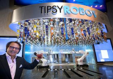 Rino Armeni, chairman of Robotic Innovations, poses by robotic bartenders in the Miracle Mile Shops at Planet Hollywood Monday, June 26, 2017. The in the Tipsy Robot automated bar is scheduled to open on Friday, he said.