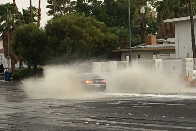 A car splashes through standing water on Eastern Avenue at Mohigan Way on Wednesday, July 19, 2017, during a thunderstorm in the Las Vegas Valley.