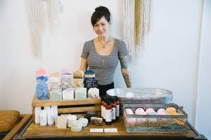 Audrey Hale of Roux and Bones Soaps stands next to a table of her handmade soap and bath products during the Maker's Market event at Sister House Collective in downtown Las Vegas, Saturday, July 15, 2017.