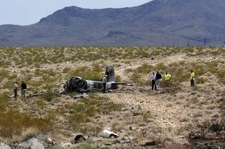 Officials look over a crash site after a vintage single-engine British-built military jet crashed and burned in the desert just after takeoff from the Henderson Executive Airport in Henderson Monday, July 24, 2017. The pilot escaped serious injury, authorities said.