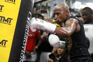 Floyd Mayweather Jr. hits a heavy bag during a workout at the Mayweather Boxing Club Thursday, Aug. 10, 2017.