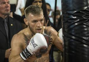 Conor McGregor hits a bag during a media workout before ...
