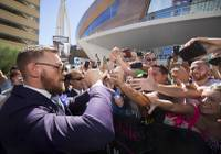 UFC lightweight champion Conor McGregor of Ireland greets fans as he arrives at Toshiba Plaza Tuesday, Aug. 22, 2017.