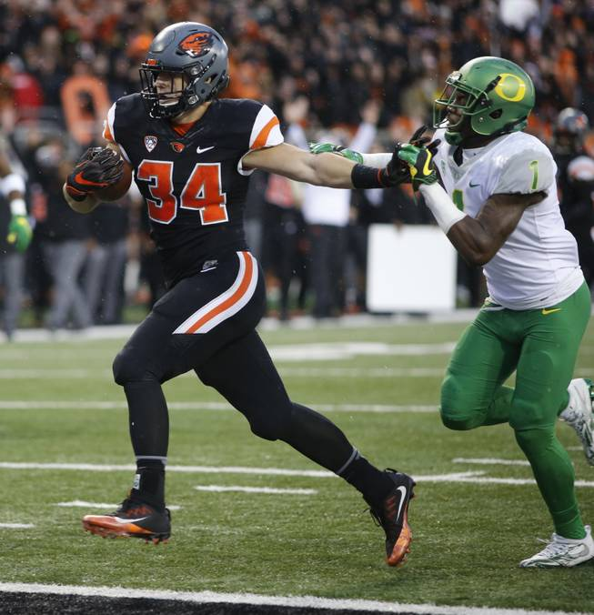 Oregon State running back Ryan Nall (34) stiff-arms his way past Oregon's Arrion Springs (1) for a touchdown in the second half an NCAA college football game in Corvallis, Ore., Saturday Nov. 26, 2016.
