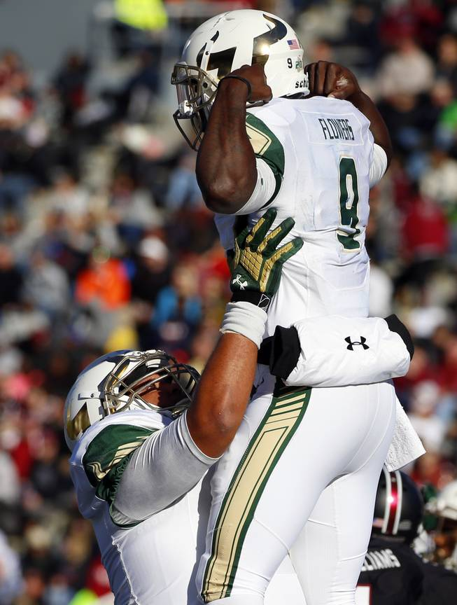 South Florida quarterback Quinton Flowers (9) is hoisted by a teammate celebrating his touchdown against South Carolina during the first half of the Birmingham Bowl NCAA college football game, Thursday, Dec. 29, 2016, in Birmingham, Ala.