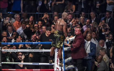 Super welterweight Floyd Mayweather Jr. celebrates is win over Conor McGregor standing on the ropes above the crowd at the T-Mobile Arena on Saturday, August 26, 2017.