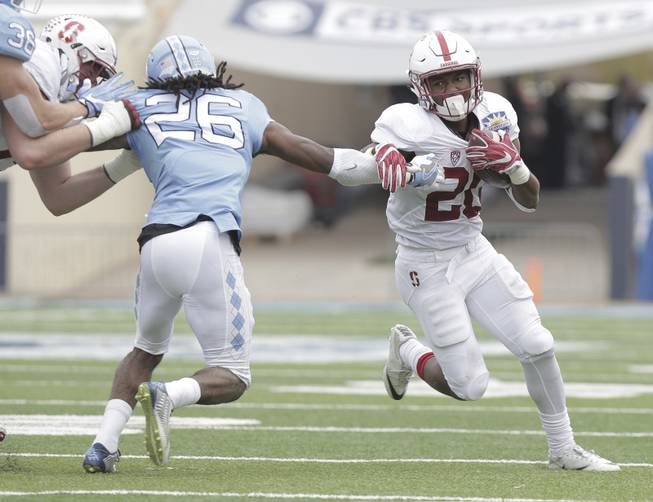 Stanford running back Bryce Love, right, shrugs off North Carolina safety Dominiqie Green in the second quarter of the Sun Bowl NCAA college football game, Friday, Dec. 30, 2016, in El Paso, Texas.