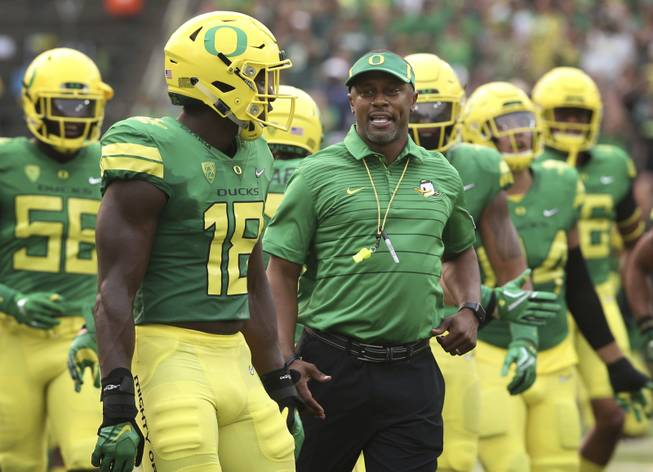 Oregon coach Willie Taggart, center, joins his team as they take the field for an NCAA college football game against Southern Utah on Saturday, Sept. 2, 2017, in Eugene, Ore.