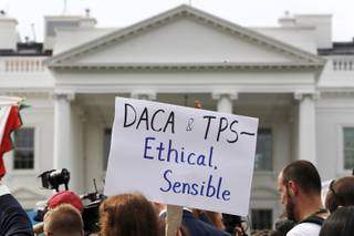 A person holds up a sign in support of the Deferred Action for Childhood Arrivals, known as DACA, and Temporary Protected Status programs during a rally in support of DACA and TPS outside of the White House, in Washington, Tuesday, Sept. 5, 2017. President Donald Trump's administration will