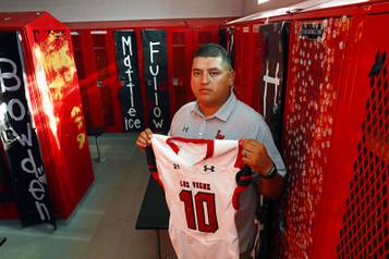 Las Vegas High School head coach Erick Capetillo poses by a locker kept vacant in memory of Eddie Gomez at the school Thursday, Sept. 7, 2017. Gomez, a player with the Las Vegas High School football team, died in 2003, two days after suffering a head injury in a playoff game. Capetillo was also a player on the team at the time.