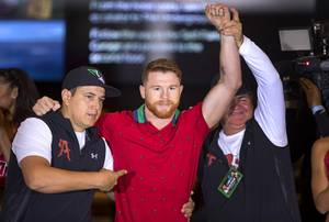 Boxer Canelo Alvarez of Mexico poses with co-trainer Eddy Reynoso, left, and trainer Jose