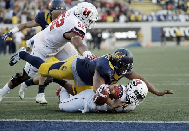 Utah running back Zack Moss, bottom, is stopped just shy of the end zone by California defensive tackle James Looney on the last play of an NCAA college football game Saturday, Oct. 1, 2016, in Berkeley, Calif. California won 28-23.