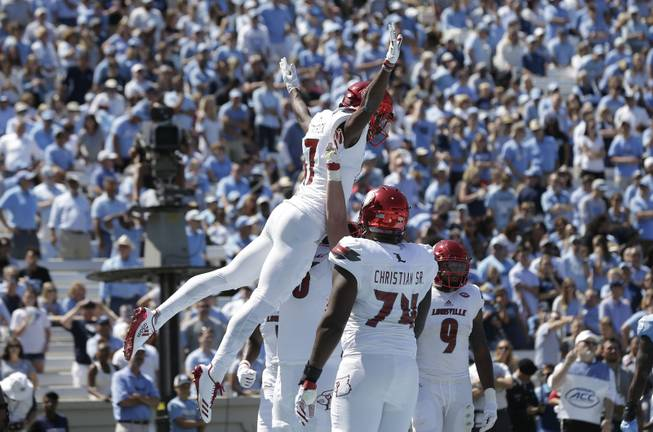 Louisville's Dez Fitzpatrick jumps while celebrating with teammates following his touchdown against North Carolina during the first half of an NCAA college football game in Chapel Hill, N.C., Saturday, Sept. 9, 2017.