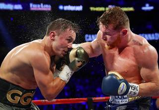 WBC/WBA/IBF middleweight champion Grennady Golovkin, left, of Kazakhstan takes a punch from Canelo Alvarez of Mexico during their title fight at T-Mobile Saturday Saturday, Sept. 16, 2017. The boxers fought to a draw and Golovkin retained his titles.