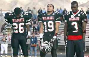 Las Vegas High School football players Stanley Copeland, Jacob Robertson and Greg Hansborough observe a moment of silence for teammate Edward Gomez before the start of their state semifinal game against Palo Verde Saturday, November 29, 2003. Gomez died as a result of injuries suffered in a game a week earlier.