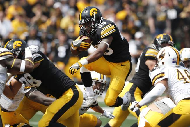 Iowa running back Akrum Wadley (25) leaps past Wyoming linebacker Cassh Maluia, right, during the second half of an NCAA college football game, Saturday, Sept. 2, 2017, in Iowa City, Iowa. Iowa won 24-3.