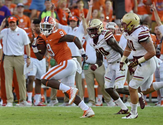 Clemson's Travis Etienne outruns Boston College's Isaac Yiadom, center, and Ty Schwab to score a 50 yard touchdown during the second half of an NCAA college football game Saturday, Sept. 23, 2017, in Clemson, S.C. Clemson won 34-7.