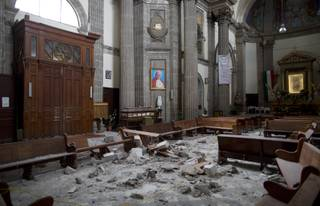 Debris from the cupola of the Our Lady of Angels Church is scattered on the wooden pews and floor below a framed image of Pope John Paul II, in Mexico City, Sunday, Sept. 24, 2017. Our Lady of Angels Church has survived several major earthquakes, but Tuesday's magnitude 7.1 shake appears to have been the death knell for the Mexico City building's historic cupola. (AP Photo/Enric Marti)