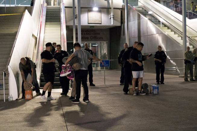 Metro Police conduct a search on people bringing supplies to the people taking refuge inside the Thomas & Mack following a mass shooting at the Route 91 music festival along the Las Vegas Strip, Monday, Oct. 2, 2017, in Las Vegas.