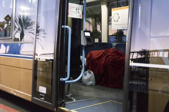 A woman sleeps inside an RTC bus parked outside the Thomas & Mack Center where people took refuge following a mass shooting at the Route 91 music festival along the Las Vegas Strip, Monday, Oct. 2, 2017, in Las Vegas.