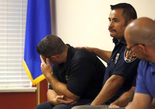 Clark County firefighter Jesse Gomez, center, supports Henderson firefighter Anthony Robone during a news conference at the International Association of Firefighters Union Hall, Local 1285, Tuesday, Oct. 3, 2017. Robone's older brother Nick, an assistant hockey coach at UNLV, was hit by gunfire at the Route 91 Harvest festival on Sunday when gunman Stephen Paddock opened fire on the crowd.