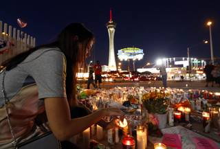 Dashenka Giraldo of Las Vegas lights candles at a makeshift memorial for shooting victims at the Las Vegas Strip and Sahara Avenue Wednesday, Oct. 4, 2017.