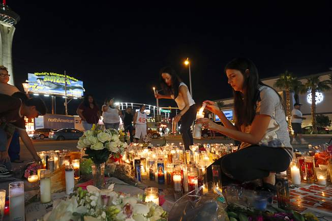Elisabeth Apcar, center, and her cousin Dashenka Giraldo, both of Las Vegas, light candles at a makeshift memorial for shooting victims at the Las Vegas Strip and Sahara Avenue Wednesday, Oct. 4, 2017.