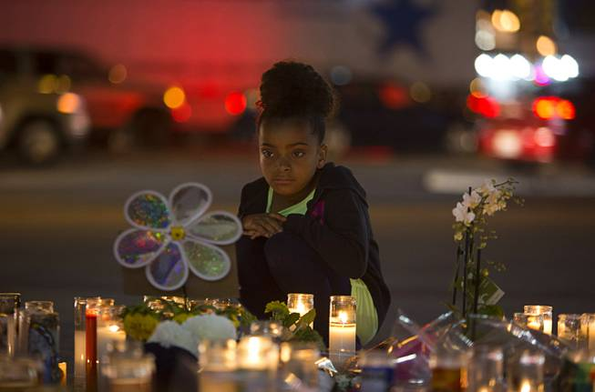 A girl looks over a makeshift memorial for shooting victims at the Las Vegas Strip and Sahara Avenue Wednesday, Oct. 4, 2017.
