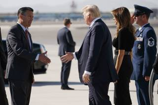 Nevada Gov. Brian Sandoval, left, greets President Donald Trump and first lady Melania Trump as they arrive Wednesday, Oct. 4, 2017, at Las Vegas McCarran International Airport to meet with victims and first responders of the mass shooting.