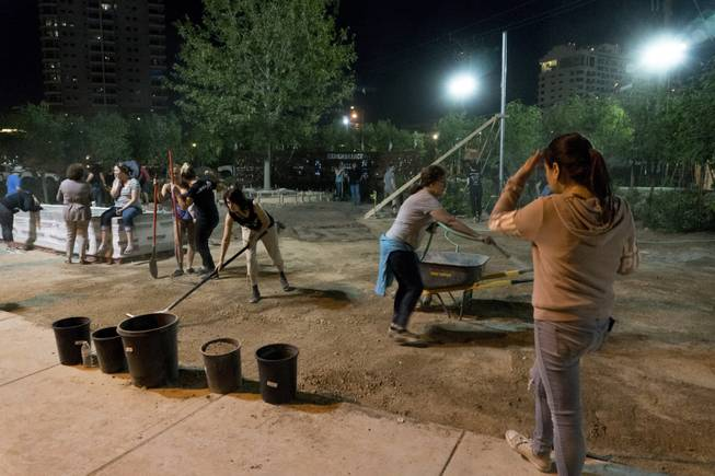 Volunteers work on a community healing garden being created in response to the Oct. 1 mass shooting, Thursday evening, Oct. 6, 2017. Jay Pleggenkuhle and Daniel Perez of Stonerose Landscapes organized the effort the day after the shooting. Through volunteers and donations, the garden should open on First Friday, five days after the tragic event.