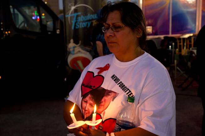 "Gloria Avila holds back tears as she holds candles Friday Oct. 6, 2017, during a vigil at First Friday, for the memory of the victims in the Route 91 Havest Festiva. Avila's neice Denise Cohen and her boyfriend ""Bo"" Taylor were killed in the mass shooting."