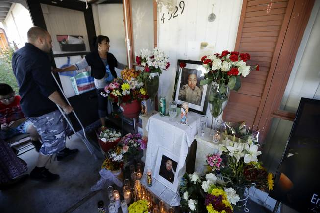 Angelica Silva, the mother of mass shooting victim and security guard Erick Silva, leads Jeff Bachman, a fellow security guard who was shot in the leg during last Sunday's mass shooting, past a candle-lit memorial with photos of Erick and flowers to honor him at his home Friday, Oct. 6, 2017, in Las Vegas.