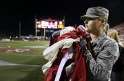 Airman 1st Class Tori Glover from Nellis Airforce base waits to display a giant American flag with other airmen and athletes before a UNLV football game against San Diego State at Sam Boyd Stadium Saturday, Oct. 7, 2017.